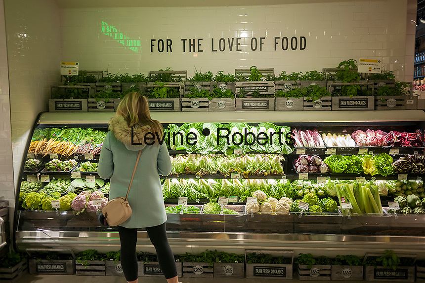 Shopper in the produce department in the new Whole Foods Market opposite Bryant Park in New York on opening day Saturday, January 28, 2017. The store in Midtown Manhattan is the chain's 11th store to open in the city. The store has a large selection of prepared foods from a diverse group of vendors inside the store.  (© Richard B. Levine)