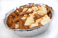 A poutine over a white background. Poutine is a French Canadian dish consisting of French fries topped with fresh cheese curds and covered with hot gravy.