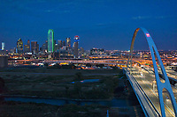 Captured this colorful aerial image of the Dallas skyline with the Margaret McDermott bridge or IH30 in downtown as it crosses the Trinity River after dark.  We like the red, white and blue of the Reunion Tower, and the green outline of the Bank of America building in downtown. The bridge is part of the Trinity Project and was designed by architect Santiago Calatrava. We like the way this shows off the architecture of the bridge and the city in this compacted view of downtown from over the Trinity river. This is just one of many of our Dallas Skyline Stock images along with our aerial drone photos,