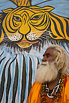 """Indian holy man, """"Sadhu"""" in front of large wall tiger painting (mural);  Varanasi has been a cultural and religious center in northern India for several thousand years, Varanasi, Uttar Pradesh, India --- Model Released"""