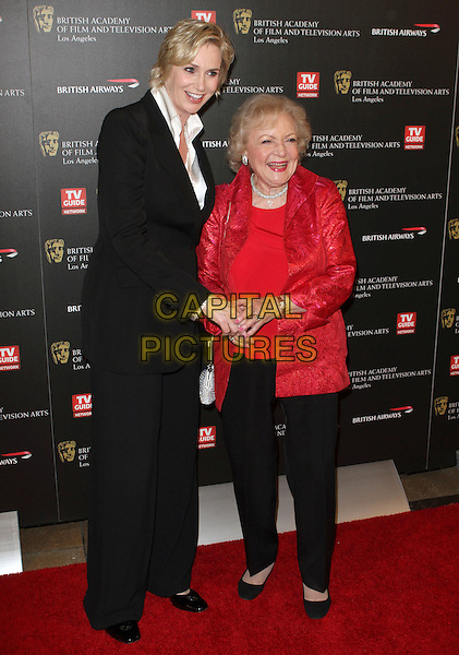 JANE LYNCH & BETTY WHITE .BAFTA Los Angeles 2010 Britannia Awardsz held at The Hyatt Regency Plaza Hotel, Century City, CA, USA, .4th November 2010..full length black trousers suit jacket white shirt red holding hands .CAP/ADM/KB.©Kevan Brooks/AdMedia/Capital Pictures.