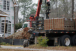 A small pallet loader in action moving a stack of bricks while a specialized crane moves tons of wallboard in the background.  Ironically, work can't finish fast enough on constructing the 'teardown' houses in Atlanta's depressed housing market.