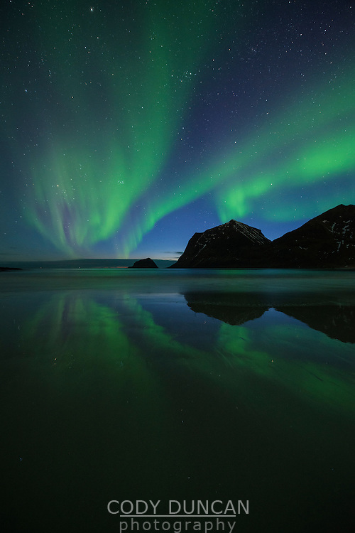Spring northern lights reflection on Vik beach, Vestvågøy, Lofoten Islands, Norway