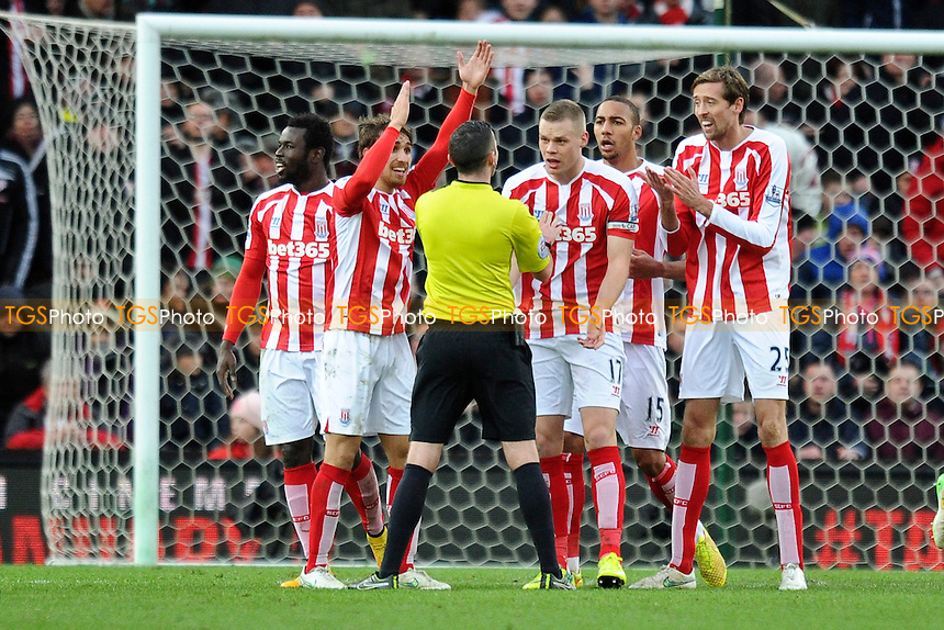 Stoke players surround referee Michael Oliver to appeal for a handball decision that wasn't given - Stoke City vs Manchester United - Barclays Premier League Football at the Britannia Stadium, Stoke-on-Trent - 01/01/15 - MANDATORY CREDIT: Greig Bertram/TGSPHOTO - Self billing applies where appropriate - contact@tgsphoto.co.uk - NO UNPAID USE