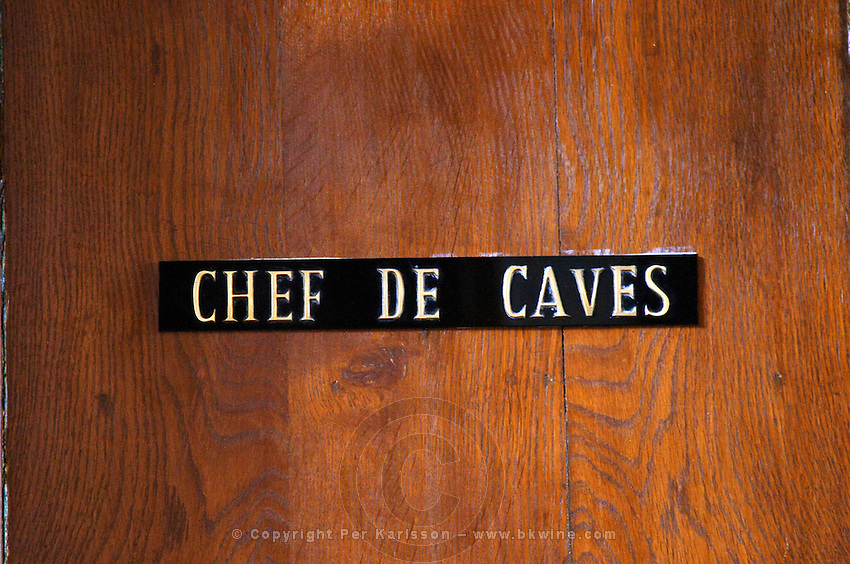 A sign on a wooden door saying chef de caves (chief winemaker or responsible for production), Champagne Ruinart, Reims, Champagne, Marne, Ardennes, France, low light grainy grain