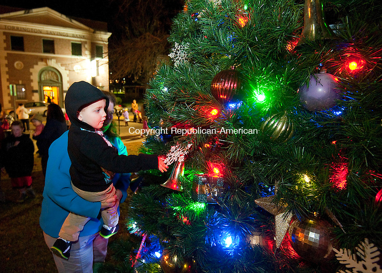 TORRINGTON, CT--- -112715JS04--Charlie Weinbach, 3, of Simsbury, being held by his aunt Kathryn Rosenfield, admires ornaments on the Christmas tree in front of Torrington City Hall during Light Up Main events in downtown Torrington on Friday. Many of the events were hosted by Torrington Parks and Recreation Department.  The family were in town to visit relatives during the holiday season. <br />  Jim Shannon Republican-American
