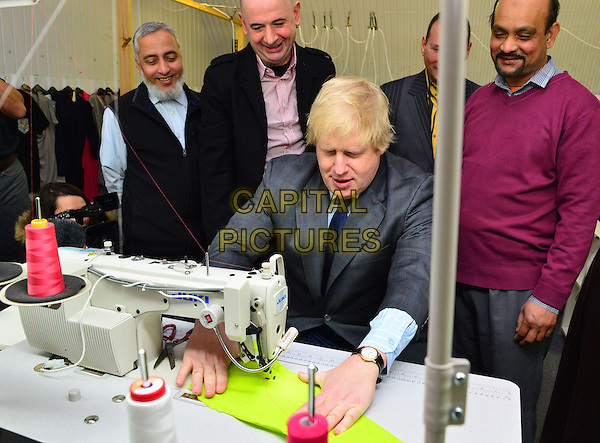 Boris Johnson .visits newly established clothes manufacturer in East London, East End Manufacturing Ltd., London, England..26th February 2013.half length blue shirt grey gray tie suit sewing machine table sitting looking down.CAP/BF.©Bob Fidgeon/Capital Pictures.