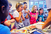 """PIZZA FISH? - Alex Domann teaches Pierce 2nd graders about fish by showing them a dissected catfish, which elicited some reactions from the students, as well as the comment, """"It looks like Pizza"""" about the insides of the catfish. 'Oceans and Motions' led by Fauquier High students for 2nd grade pathfinders from each elementary school in the county Friday at FHS in Warrenton , VA.  --Staff Photo/Randy Litzinger"""
