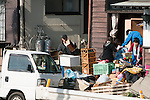 Mar. 13, 2011 - Kita-Ibaraki, Japan - A family takes out whatever they have left out of their destroyed home two days after the 8.9 magnitude earthquake struck followed by a tsunami that hit the north-eastern region. The death toll is currently unknown with casualties that may run well into the thousands.