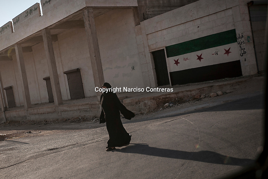 A Syrian woman walks in the streets of Maari, a village under control of the opposition fighters which is under shelling by Syrian army in northern of Aleppo province.