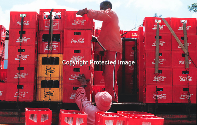 PAPRODU12020 Business Shopping  Zimbabwe.  Men loading crates of Coca Cola on to a truck. Products.©Per-Anders Pettersson/iAfrika Photos