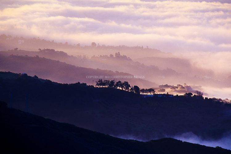 The Pacific Ocean marine layer (fog) rolls in on a summer morning highlighting the hills of Monticito, CA.