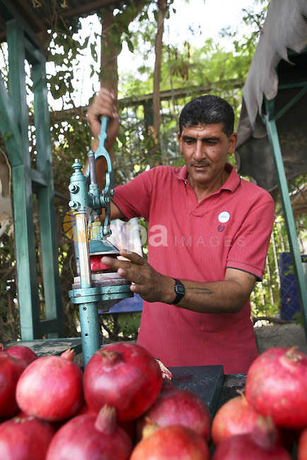 A Palestinian worker presses pomegranates in his shop , in West Bank city of Jericho , on Oct. 11.2010 . Jericho is one of the oldest continuously inhabited cities in the world, with evidence of settlement dating back to 9000 BC,it has a population of over 20,000 Palestinians. Situated well below sea level on an east-west route 16 kilometres (10 mi) north of the Dead Sea, Jericho is the lowest permanently inhabited site on earth . Photo by Eyad Jadallah