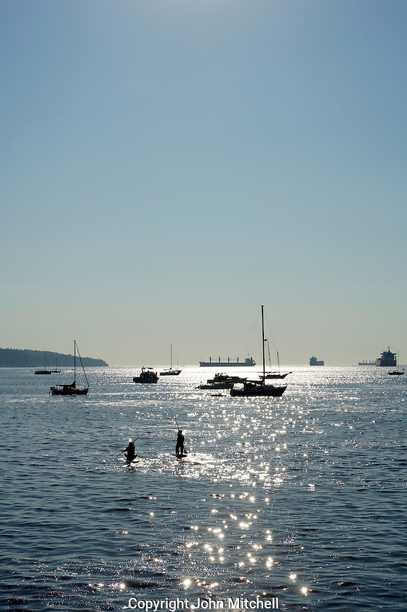Two paddle boarders sailing out into English Bay with sunlight on water, Vancouver, BC, Canada