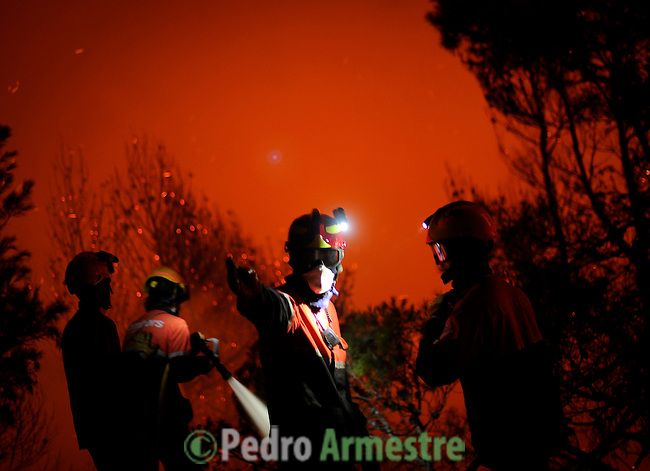 A firefighter of Alcoy and Elda tries to extinguish a fire in Torre de Macanes near Alicante, on August 13, 2012. One person was killed and three injured Sunday as firefighters battled wildfires across Spain, authorities said, the latest victims in a sweltering summer of forest blazes. (c) Pedro ARMESTRE