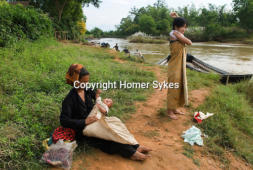 Mother with young baby, she has just washed him in the river. In Dein or Indein village Inle Lake. Myanmar (Burma.) 2006.