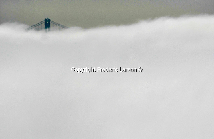 The summer fog engulfs the Bay Bridge towers as seen from Sausalito, California.