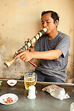 VIETNAM, Hanoi, Bathranag Village, a man smokes and drinds a beer at a small smoke shop
