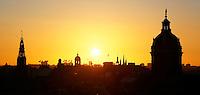 Nederland  Amsterdam 2016 . Amsterdam bij zonsondergang. Rechts de Nicolaaskerk. Links de Oude Kerk. Foto Berlinda van Dam / Hollandse Hoogte