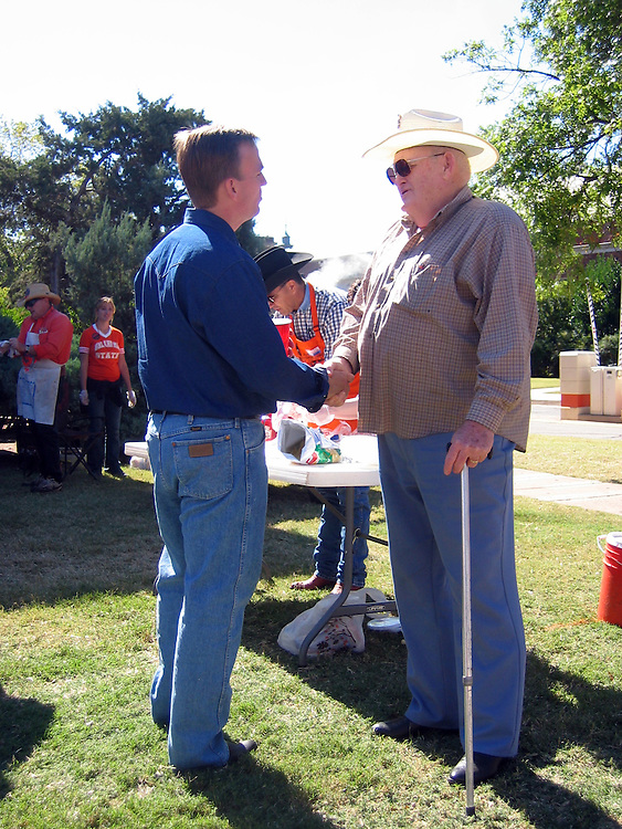 Rep. Brad Carson meets supporter Jack Warren at his campaign's tailgate during the Oklahoma State University homecoming festivities in Stillwater Saturday.