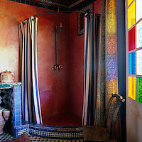 In the corner of the bathroom the shower is pink tadelakt and the stained glass windows cast pretty colours onto the curtains