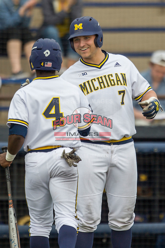 Michigan Wolverines catcher Harrison Wenson (7) greets teammate Ako Thomas (4) after he scored against the Toledo Rockets on April 20, 2016 at Ray Fisher Stadium in Ann Arbor, Michigan. Michigan defeated Bowling Green 2-1. (Andrew Woolley/Four Seam Images)