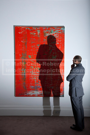 01/02/2012. LONDON, UK. A member of Sotherby's staff looks at Gerhard Richter's, Abstraktes Bild, 'rot', ahead of an auction of Impressionist and Modern Art held on the 15th of February 2012. The piece is estimated to raise £2,500,000-3,500,000. Photo credit: Matt Cetti-Roberts