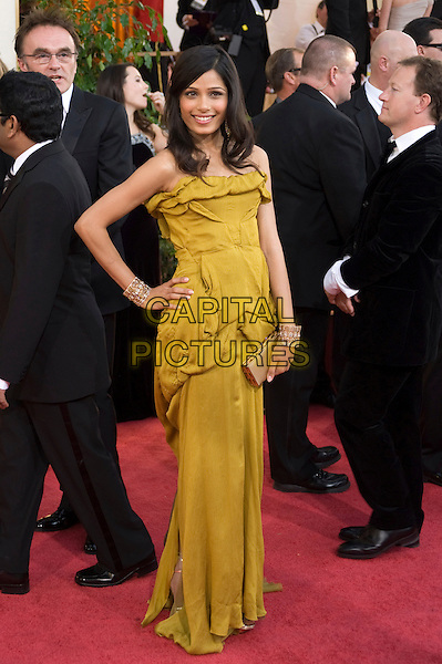 FREIDA PINTO.Arrivals at the 66th Annual Golden Globe Awards held at the Beverly Hilton Hotel, Beverly Hills, California, USA..January 11th, 2009.*Editorial Use Only* .globes full length yellow dress hand on hip gold gathered clutch bag .CAP/AWF/HFPA .Supplied by Capital Pictures.