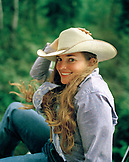 USA, Montana, portrait of a cowgirl in cowboy hat smiling, Mountain Sky Guest Ranch