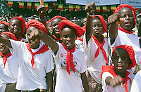 Mali. Province of Segou. Niono. October 16 2003. Worlwide food day. The crowd waits under the malian flag (green, yellow and red) for the arrival of the malian president Amadou Toumani Toure (ATT). The young girls are dressed with western clothes (one has a swiss Tshirt with a swiss flag). They sing and hold their arms up and give a raised-fist salute.  © 2003 Didier Ruef