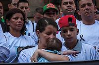 SÃO PAULO, SP, 28.10.2014-PROTESTO PELA MORTE DO MOTORISTA  -  A esposa do motorista morto segura um de seus filhos no colo enquanto é consolada por um dos filhos durante ato contra a morte de seu marido. Motoristas e cobradores realizam ato em protesto a morte do motorista John Carlos Soares Brandão. O protesto acontece na tarde desta terça-feira (28), na região central de São Paulo. (Foto: Taba Benedicto/ Brazil Photo Press)