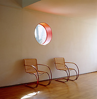 Circular details such as this porthole window and the curved design of a pair of Mies van der Rohe armchairs soften the modernist lines of the house