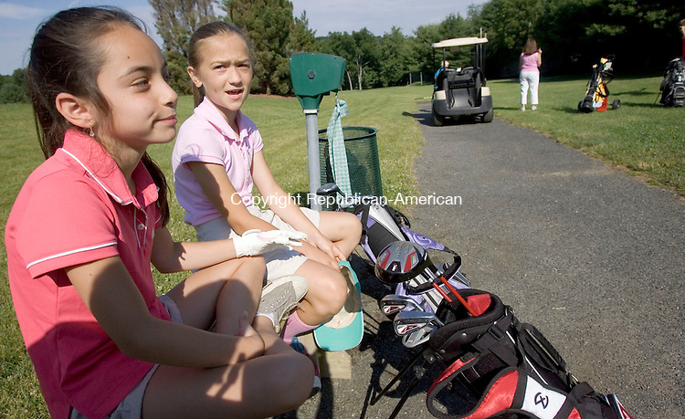 SOUTHBURY CT. 30 June 2014-063014SV05-From left, Katie Sheehan, 10, and Avery Lenczewski, 9, both of Southbury wait their turn to tee off during a youth golf league tee time at Gainfield Farms Golf Course in Southbury Monday.<br /> Steven Valenti Republican-American