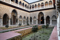 General low angle view of the arcade courtyard at Patio de las Doncellas (Courtyard of the Maidens), Real Alcazar, Seville, Spain, looking at the upper portico, pictured on December 24, 2006, in the afternoon. The upper storey of the Patio was built by Luis de Vega under the reign of Charles V, 1540-1572. The Real Alacazar was commissioned by Pedro I of Castile in 1364 to be built in the Mudejar style by Moorish craftsmen. The palace, built on the site of an earlier Moorish palace, is a stunning example of the style and a UNESCO World Heritage site. The garden in this courtyard is of a Moorish plan. Picture by Manuel Cohen.