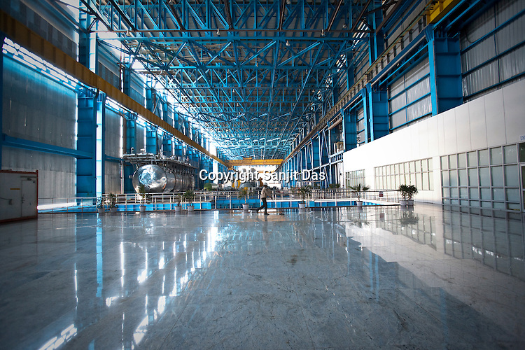 An employee sweeps the floor of the Unit 1 of the Adani Power plant in Mundra port industrial city of Gujarat, India. Indian power companies have handed out dozens of major contracts to Chinese firms since 2008. Adani Power Ltd have built elaborate Chinatowns to accommodate Chinese workers, complete with Chinese chefs, ping pong tables and Chinese television. Chinese companies now supply equipment for about 25% of the 80,000 megawatts in new capacity.