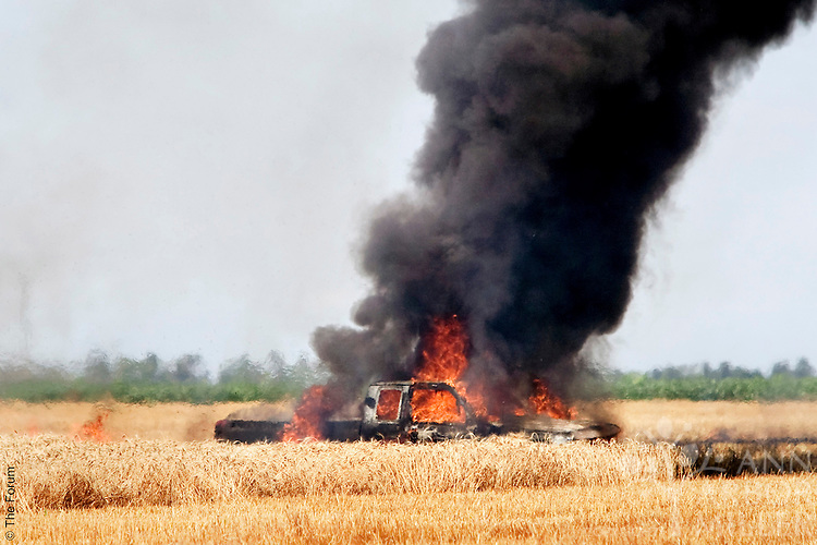 An unoccupied 1995 Dodge pick-up truck burns in a wheat field on Aug. 14, 2008, about one mile west of Sheldon, N.D. Enderlin (N.D.) Assistant Fire Chief Gerald Schumacher said the fire started after the owner, farmer Eugene Krueger of rural Sheldon, parked the truck in the field. He said the truck's underside, still hot from a running engine, sparked a fire in the field which eventually engulfed the entire vehicle. Volunteer firefighters spent 10 to 15 minutes extinguishing the blaze, but the truck was a total loss. Schumacher said no one was injured, but the blaze scorched nearly an acre around the truck. Krueger was not on the scene when the fire began; however, he returned promptly to the field after noticing a plume of thick black smoke.