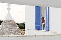 A guest enjoys the fresh air at Villa Cenci from the balcony of her bedroom