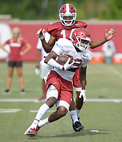 NWA Democrat-Gazette/ANDY SHUPE<br /> Arkansas receiver Gary Cross carries the ball after making a catch as defensive back Britto Tutt defends Tuesday, Aug. 7, 2018, during practice at the university practice fields in Fayetteville. Visit nwadg.com/photos to see more photographs from the practice.