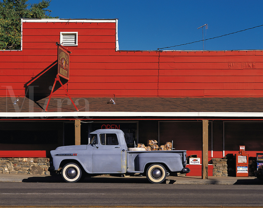 Old-style grey pick-up truck parked in front of red-painted store, California, US