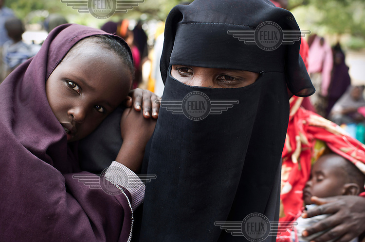 A woman holds her child as they wait to receive food at a distribution point in Mogadishu.