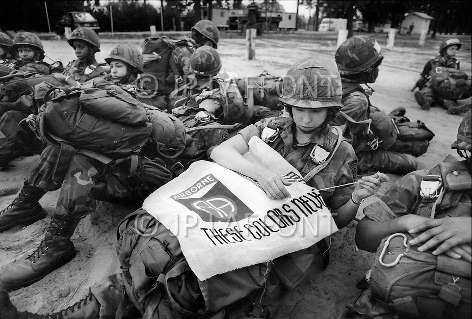 Fort Bragg, NC. June, 1980. <br /> In a group of female paratroopers of the 82nd Airborne Division, one soldier embroiders a flag with the Airborne&rsquo;s insignia with the phrase &lsquo;These Colors Never Run&rsquo;.<br /> Fort Bragg, Caroline du Nord. Juin, 1980. <br /> La 82eme division a&eacute;roport&eacute;e est le fer de lance des USA, toujours pr&ecirc;t &agrave; partir. Les femmes doivent se plier &agrave; un entrainement intensif. Elles le font avec courage, mais gardent aussi leur passe temps, ce soldat brode la devise de sa division avant un saut d&rsquo;entrainement.