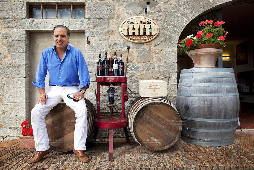 Italy. Tuscany. Villa A Sesta is part of the village Castelnuovo. Riccardo Tattoni is seated on a wooden barrel at the entrance of the wine shop and cellar from Agricola Tattoni Villa A Sesta. 18.09.10 © 2010 Didier Ruef