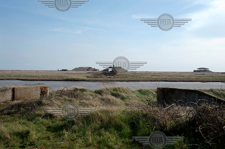 The view that W G Sebald describes in his classic book the Rings of Saturn, as he approaches the bridge into Orfordness, Suffolk. The bridge is no longer there but, visible in the background, one the abandoned and decaying secret Atomic Weapons Research Establishment laboratories mentioned in Sebald's book remains....