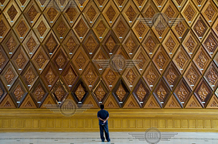 A man looks at a wall inlaid with samples of the hardwoods found in Burma's forests in the official reception hall of  the Pyidaungsu Hluttaw or Assembly of the Union (Burmese parliament).