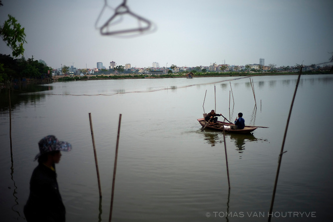 Boys play in a boat while another boy looks on in Hanoi, VIetnam on 9 March 2010.
