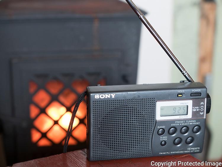 Liten FM-radio foran ovenen på hytta Helheim på Varangerhalvøya. ---- Small FM-radio.