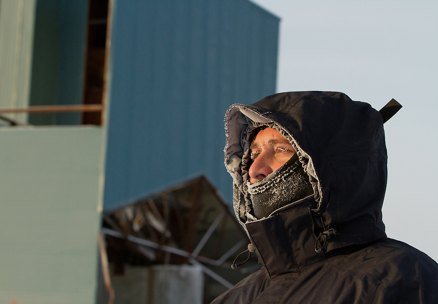 A man stands with frozen eyelashes and frost around his mouth in sub-zero conditions.