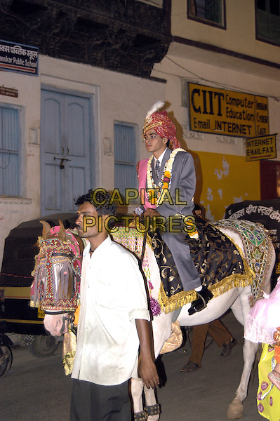 A Groom rides a horse to his wedding,. in traditional Indian style..atmosphere gv general view travel ride riding.CAP/CJ.©Chris Joseph/Capital Pictures.