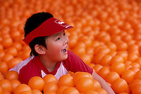 Young Asian Boy playing in Room filled with Orange Balls (No Model Release Available)