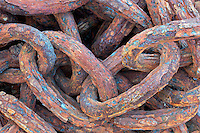Chain in old junkyard of car and truck parts at seashore. Kauai, Hawaii.